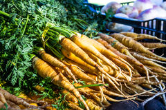 Open Air Farmers Market. Stack of bunches of fresh local organic carrots sitting on table for sale at local farmers market royalty free stock image