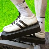 Open Air Fitness. Man's Legs On A Fitness Machinery Against Green Grass Background Royalty Free Stock Photos