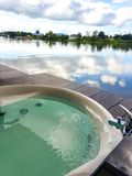 Open air Jacuzzi beside the natural river and blue sky view stock images