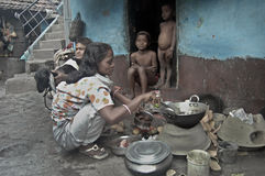 Slum life in India. A woman is cooking lunch for her family in open air just outside of her room in the slum area of Kolkata which is surrounded by tanneries Royalty Free Stock Photography