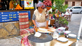 The open air kitchen. ANTALYA, TURKEY - MAY 6, 2017: The senior woman - the cook of the restaurant, prepares gozleme, traditional Turkish village flatbread, she stock video footage