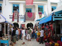 Open-air market in Hammamet, Tunisia. HAMMAMET, TUNISIA - SEPTEMBER 25, 2008: Tourists and salesmen at the open-air market in Hammamet, bargaining for leather Stock Image