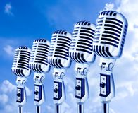 Open Air Mics. Row Of Retro Microphones Against Sky Royalty Free Stock Photos