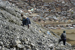 Open air mining in colorful mountains of Bolivia. Indian women, Bolivian Indians, searching between the waste of mine Corporacion Minera de Bolivia in the Andes Royalty Free Stock Image