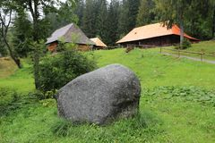 Open Air Museum of ancestry village in Slovakia, Zuberec. Stone on green meadow in Open Air Museum of ancestry village in Slovakia, Zuberec stock photos