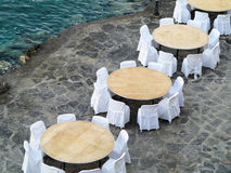 Open air restaurant near sea, white chairs and tables Royalty Free Stock Photo