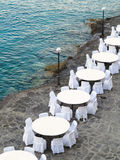 Open air restaurant near sea, white chairs and tables Royalty Free Stock Image
