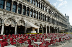 Open air restaurant in Venice, Italy. Empty chairs aligned in early morning at the street cafe or restaurant on San Marko Square in front of Doge Palace in Royalty Free Stock Photo