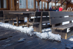 Open-air rustic wooden tables. And benches on a snowy timber deck at an outdoor restaurant at a winter ski resort stock photo