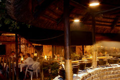 Open air safari restaurant interior at night. Open air restaurant interior at night. traditional african safari self-service meal place Royalty Free Stock Image