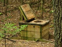 Open air toilet at a rustic forest camp site Stock Image
