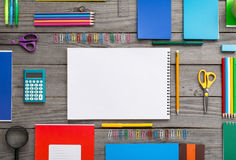 Open album with school supplies on the wooden table Royalty Free Stock Image