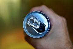 An open aluminum can of drink is compressed in a man`s hand. View from above. Shallow depth of field stock images