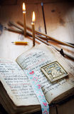 Open ancient book and burning candles Stock Photos
