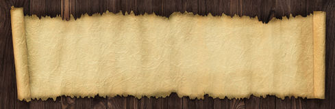 Open ancient scroll on a wooden table, panoramic paper background. Old paper on the table as a background for text royalty free stock photos