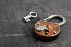 Open antique padlock with key on black Stock Photos