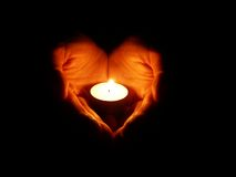 Open ardent heart #3. Heart-shaped hands holding one candle in darkness Stock Photos