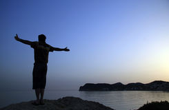 Open arms. A young man standing on a cliff with his arms wide open
