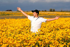 Open Arms. A young man in a field of flowers opens his arms with a happy smile Stock Photos