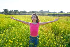 Open arms happy teen girl in spring meadow royalty free stock photography