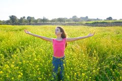 Open arms happy teen girl in spring meadow royalty free stock images