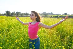Open arms happy teen girl in spring meadow royalty free stock image