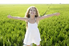 Open arms little happy girl green meadow field Royalty Free Stock Images