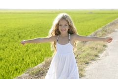 Open arms little happy girl in rice field. Open arms little happy girl green meadow rice field track royalty free stock photography