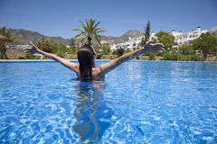 Open arms woman in pool. Brunette woman open arms in a big blue pool Royalty Free Stock Photo