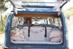 Open back of a retro camper van, with luggage and cushions Stock Photography