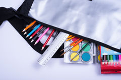 Open bag with colorful items for the school start Royalty Free Stock Photo