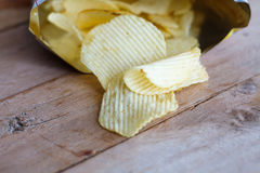 Open bag with potato chips. On wood table Royalty Free Stock Photography