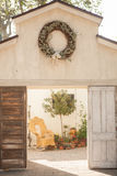 Open barn doors with wreath hanging at the top opening up to a wicker rocking chair Royalty Free Stock Photos