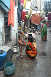 Slum life in India. A child has taken a bath from his mother, standing on a strainer of drain on the open lane in front of his house at the slum area of Kolkata Royalty Free Stock Images