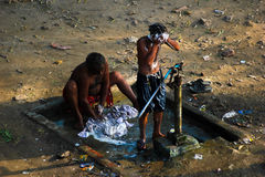 Open bath wash. 2 men taking bath in open atmosphere with a hand pump, which are common in use in villages. but they are using hand pump bank of ravi river Stock Photo