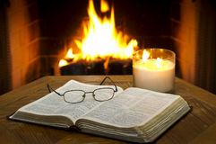Open Bible. An open Bible on a table in with a fireplace in the background royalty free stock image