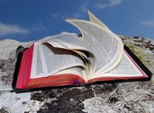 Open bible (2). Open bible on a rock with pages blown by the wind Stock Photos
