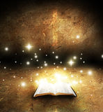Open bible. Open glowing bible with cross on grunge texture background Stock Photo