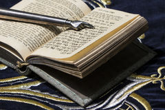 Open bible book in Hebrew with silver pointing hand. Stick on dark fabric with crown on it stock photos