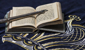 Open bible book in Hebrew with silver pointing hand. Stick on dark fabric with crown on it stock image