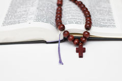 Open bible book and rosary on white Royalty Free Stock Photo