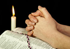 Open Bible with burning candle. And hands of praying woman Royalty Free Stock Images