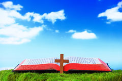 Open Bible and cross. Shine Open Bible and cross On The Grass with sky background Royalty Free Stock Photo
