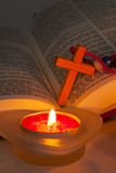 Open Bible with cross and burning candles Stock Images