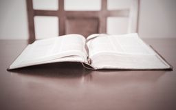 Open Bible and empty chair waiting for believer Stock Photography