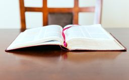 Open Bible and empty chair waiting for believer. Open Bible over a desk or table. Open word of God waiting for the pastor or believer. The need of coming back to Royalty Free Stock Images