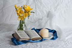 Open Bible and flowers. Candle and ribbon Royalty Free Stock Image