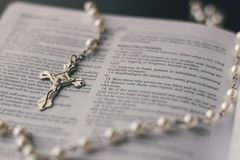 An open bible has a rosary placed on top of it. Royalty Free Stock Photography