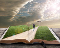 Open bible with man and cross. An open bible with grass and a man walking towards a cross Stock Photos