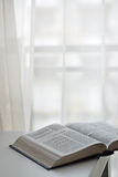 Open Bible next to the window Stock Images